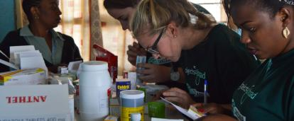 A group of Public Health volunteers prepare medication for distribution under supervision in Tanzania.